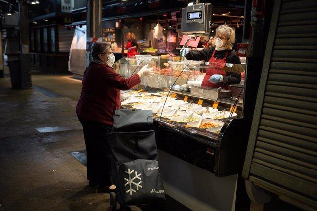 Una mujer con mascarilla compra en un puesto de un mercado y es atendida por otra mujer protegida también con una mascarilla, durante el tercer día laborable del estado de alarma por coronavirus, en Barcelona/Catalunya (España) a 18 de marzo de 2020.