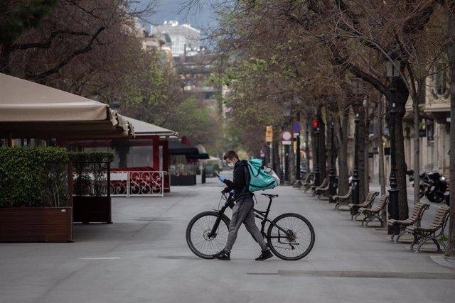 Un trabajador de Deliveroo en bicicleta por una calle de Barcelona, vacía durante el primer día laborable de la segunda semana desde que se decretó el estado de alarma en el país a consecuencia del coronavirus.