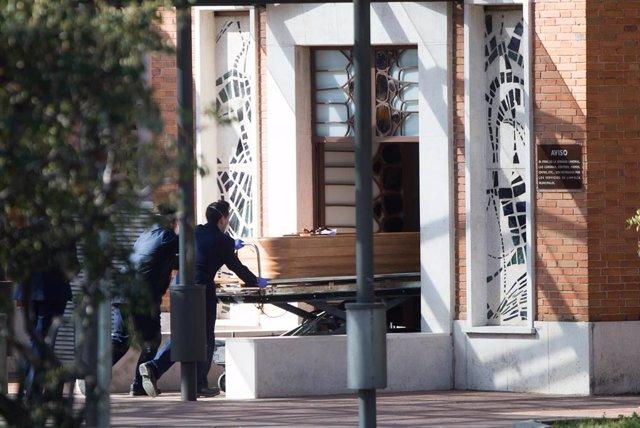 Dos trabajadores introducen un ataúd por la puerta de la funeraria municipal de Madrid