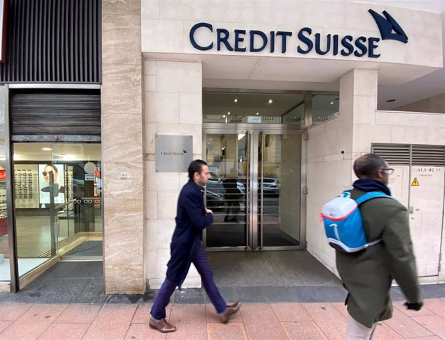 Dos hombres pasan junto a la entrada de la sede de Credit Suisse en Madrid (España), a 29 de enero de 2020.