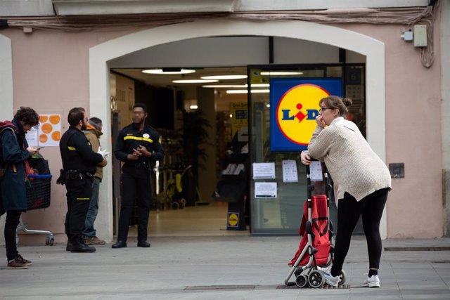 Una dona espera amb el seu carro de la compra a poder entrar a un supermercat Lidl després de les mesures d'aforament imposades per seguretat pel coronavirus