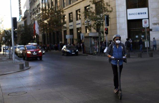 Una persona transita por Santiago de Chile con una  mascarilla para evitar la propagaci n del coronavirus
