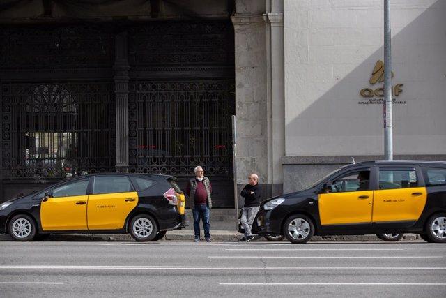 Dos taxistes esperen fora dels seus cotxes a recollir algun passatger en una estació de tren de Barcelona durant el tercer dia laborable de l'estat d'alarma per coronavirus, a Barcelona/Catalunya (Espanya) a 18 de març de 2020.