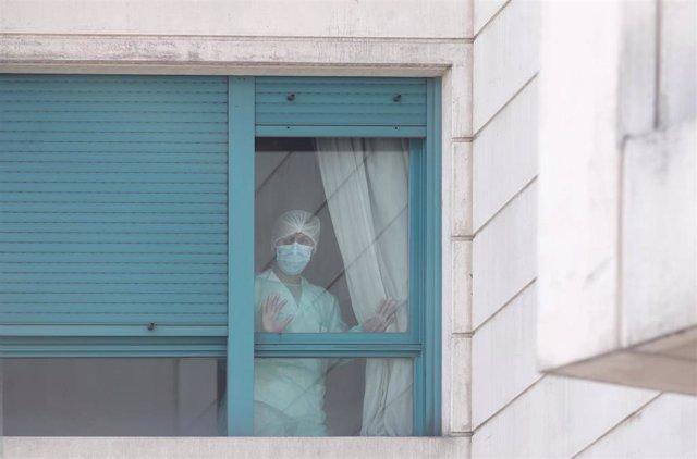 Una trabajadora del personal sanitario protegida con mascarilla se asoma por una de las ventanas de una residencia de Madrid.