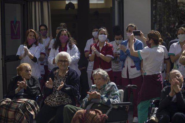 Personal y usuarios de la residencia de mayores Vitalia Kansas salen al patio durante unos minutos para celebrar que no hay ningún caso de contagio por coronavirus hasta la fecha, esta.  En Sevilla, (Andalucía, España), a 26 de marzo de 2020.