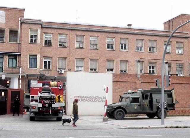 Una persona protegida con mascarilla pasea a un perro justo en el momento en el que un camión con militares de la UME a bordo llegan a la Comisaría General de Seguridad Ciudadana ubicada en Francos Rodríguez (Madrid)