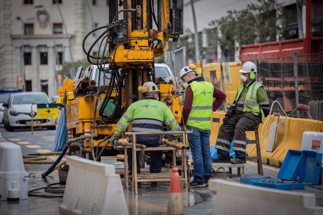 Diversos obrers treballen remodelant un carrer durant l'estat d'alarma per coronavirus, a Barcelona