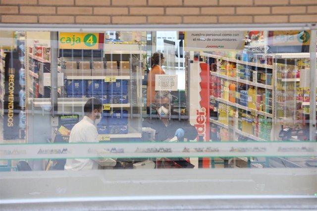 Un cajero de un supermercado AhorraMas trabaja protegido con mascarilla en plena crisis sanitaria por coronavirus donde los españoles llevan confinados en sus hogares más de una semana.