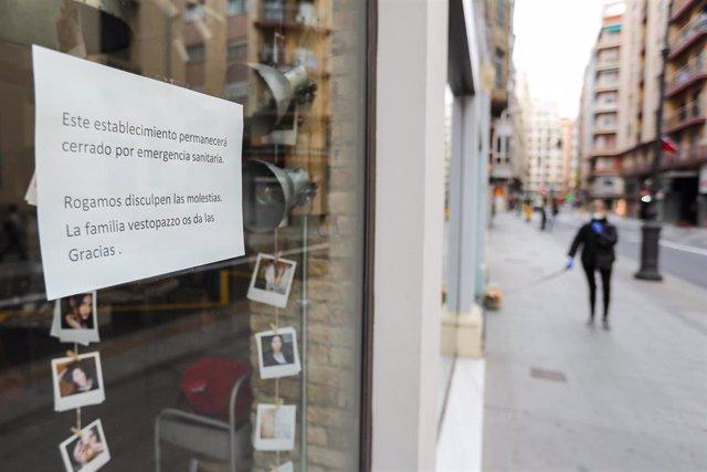 Cartel en la ventana de un establecimiento cerrado en una calle prácticamente vacía durante el segundo día laborable de la segunda semana desde que se decretó el estado de alarma en el país a consecuencia del coronavirus, en Valencia (Comunidad Valenciana