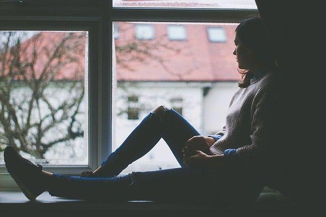 Una persona mira por la ventana desde un apartamento.