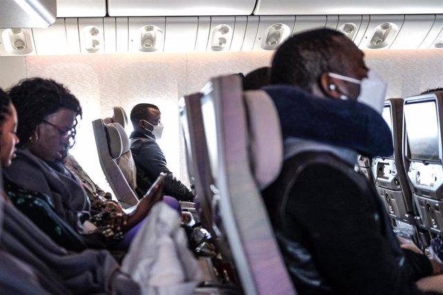 Pasajeros en un avión con mascarillas