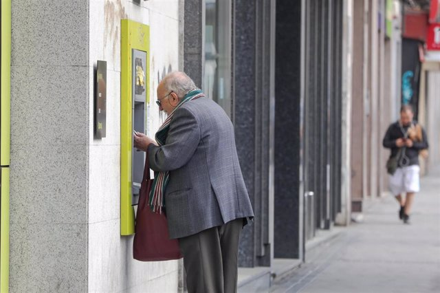 Un anciano saca dinero de un cajero de la capital tras el anuncio del estado de alarma