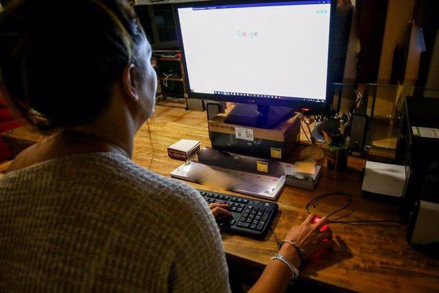 Una  mujer lee la pantalla de su ordenador, mientras trabaja