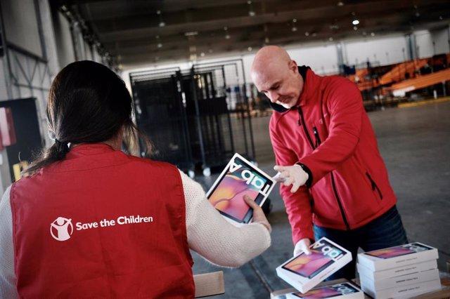 Trabajadores de la organización Save The Children ordenan las cajas de las tabletas donadas por Samsung para familias en riesgo de exclusión.