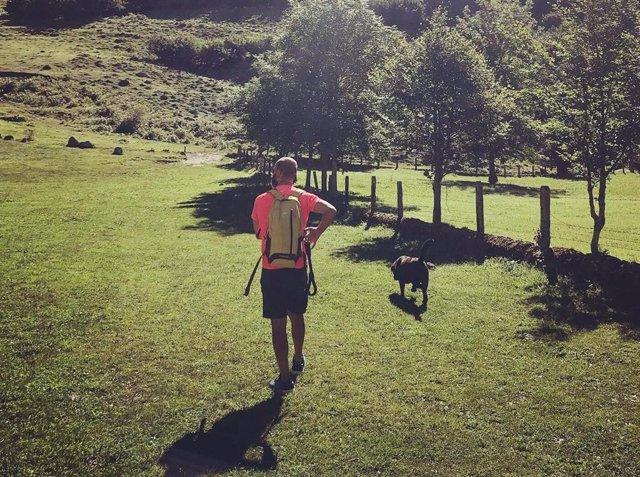 Un hombre pasea con su perro por un paraje natural.