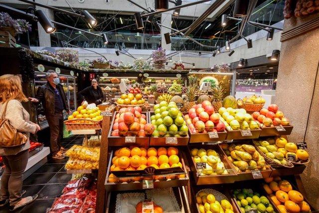 Varios clientes con mascarilla hacen la compra en un puesto de fruta en el mercado de San Antón