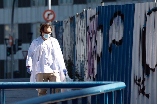Un sanitario protegido con una mascarilla y guantes sale del Hospital La Paz, centro en cuyas dependencias se ha instalado una carpa que sirve como ampliación de las Urgencias del centro.