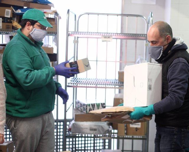 Un trabajador del Mercado municipal Barceló recoge un pedido de una empresa de reparto que le da un repartidor en plena crisis del coronavirus.