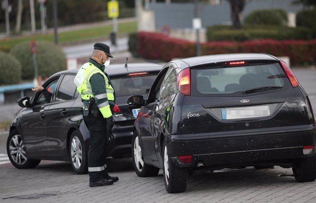 Un Guardia Civil de Tráfico para a un vehículo que se encuentra cerca de la entrada del recinto de Ifema