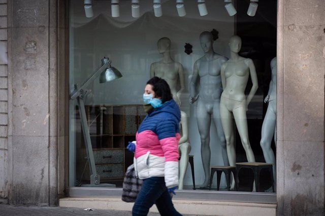 Una mujer protegida con una mascarilla pasa junto a un escaparate de una tienda cerrada durante el noveno día laborable desde que se decretó el estado de alarma en el país a consecuencia del coronavirus, en Barcelona/Catalunya (España) a 26 de marzo de