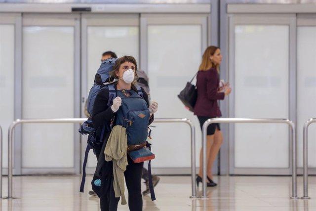Una mujer protegida con mascarilla recoge su equipaje de la Terminal 4 del Aeropuerto Adolfo Suárez-Madrid Barajas