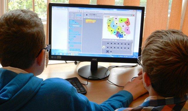 Dos niños estudian en casa por medio de un ordenador