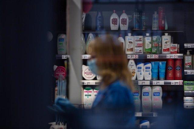 Una mujer protegida con mascarilla y guantes trabaja en una tienda durante el noveno día laborable desde que se decretó el estado de alarma en el país a consecuencia del coronavirus, en Barcelona/Catalunya (España) a 26 de marzo de 2020.