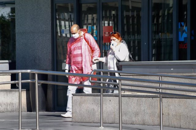 Dos personas protegidas con mascarillas salen del Hospital La Paz, centro en cuyas dependencias se ha instalado una carpa que sirve como ampliación de las Urgencias del centro y donde se atiende a pacientes sospechosos de coronavirus
