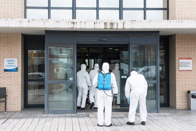 Militares de la Unidad Militar de Emergencias (UME) totalmente protegidos se disponen a entrar por la puerta de la Residencia y Centro de Día ORPEA Madrid Sanchinarro.