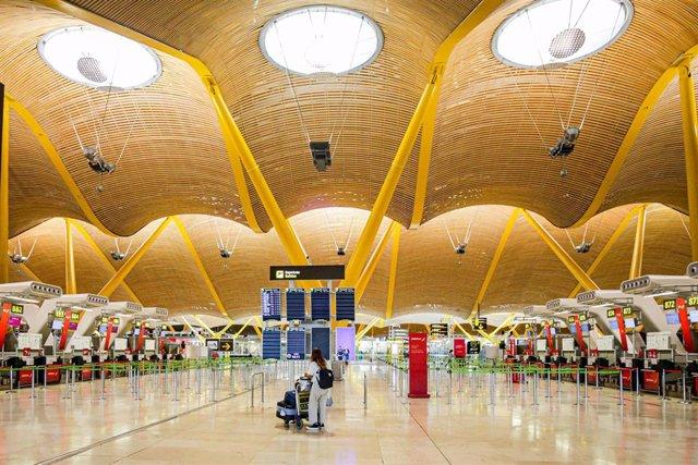 Una turista observa los paneles de la Terminal 4 del Aeropuerto Adolfo Suárez-Madrid Barajas donde el número de vuelos ha bajado notablemente.