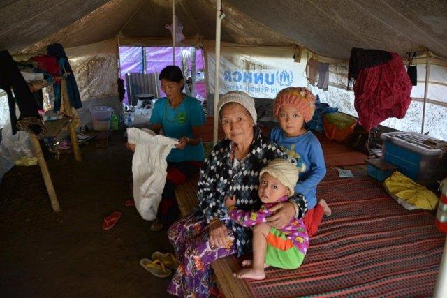 Imagen de una aldeana con sus nietos en Kachín.