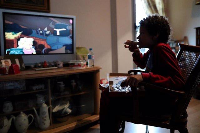 Un niño come un trozo de pizza mientras ve la televisión en su casa de Madrid durante el confinamiento.