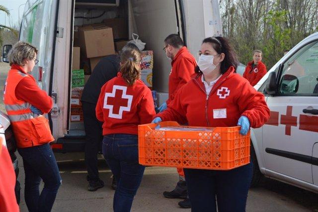 Voluntarios de Cruz Roja reparten material.