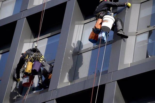 Dos operarios limpian los cristales exteriores de un edificio.