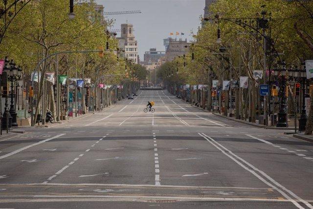 Un trabajador de Glovo en bicicleta por el Paseo de Gracia, vacío durante el primer día laborable de la segunda semana desde que se decretó el estado de alarma en el país a consecuencia del coronavirus, en Barcelona/Catalunya (España) a 23 de marzo de 202