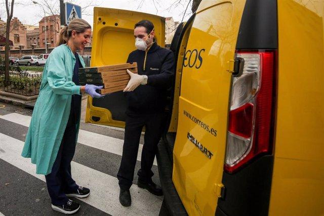 Una trabajadora sanitaria de la Clínica Ruber recoge las pizzas que le ha llevado un repartidor de Correos.