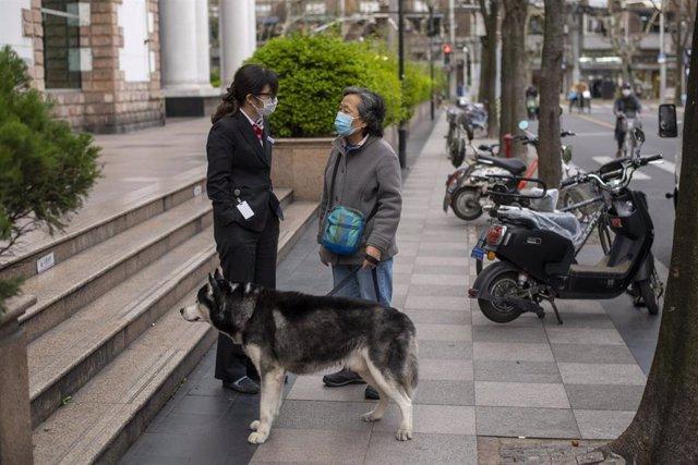 Dos mujeres con mascarilla dialogan en las calles de Shanghai.