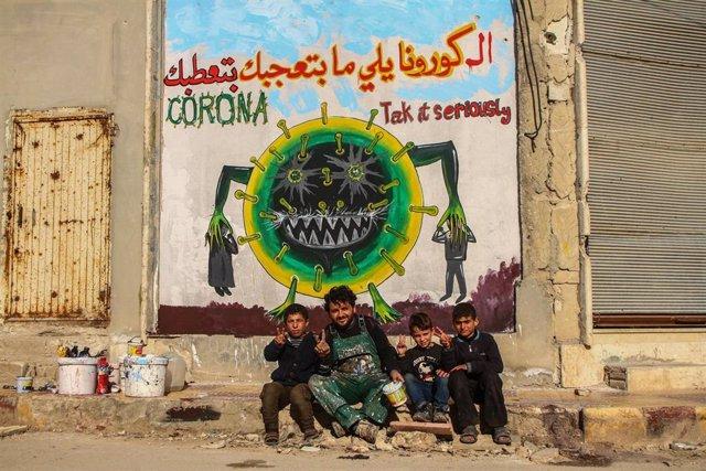 Un combatiente y varios niños frente a un mural que advierte del riesgo del coronavirus en Siria