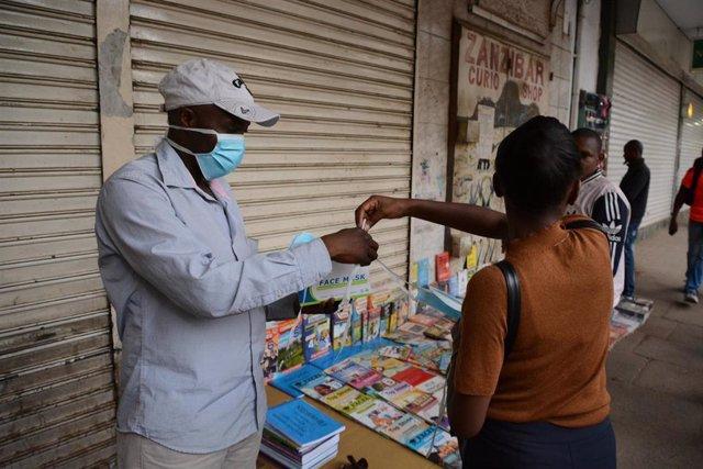 Una mujer comprando a un vendedor con mascarilla en Nairobi