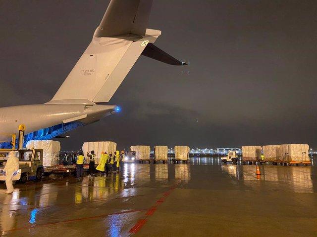 Varios trabajadores en Shangai cargan el avión del Ejército del Aire con material sanitario