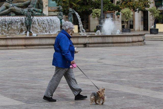Una mujer con mascarilla pasea a su perro durante el cuarto día del estado de alarma