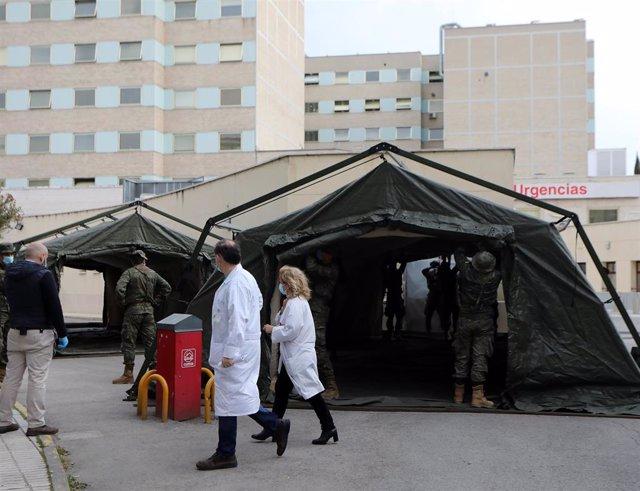 Personal sanitario pasa junto a militares en las inmediaciones del Hospital Gregorio Marañón, en Madrid