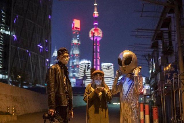 Dos ciudadanos y otra persona ataviada con un disfraz de alienígena en las calles de Shanghai.