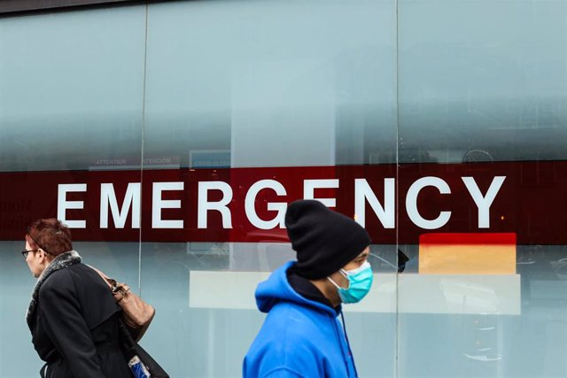 Dos neoyorquinos pasan ante las emergencias de un hospital en Nueva York
