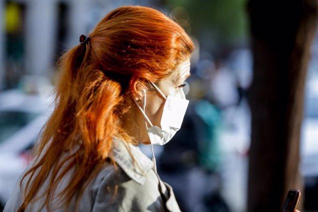 Una mujer pasea por el centro de Madrid con mascarilla como medida de protección frente al Coronavirus tras el aumento de casos en la Comunidad en las últimas horas, en Madrid (España) a 12 de marzo de 2020.