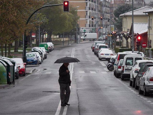 Un hombre camina bajo un paraguas durante la jornada en la que las temperaturas han bajado estrepitosamente en el segundo día de la entrada en vigor de la limitación total de movimientos salvo de los trabajadores de actividades esenciales