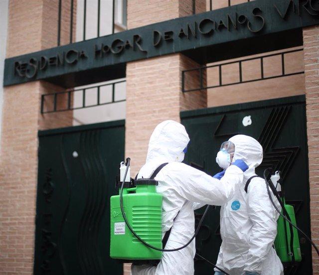 Dos militares de la UME totalmente protegidos se preparan antes de entrar en el Hogar de Ancianos Virgen de la Esperanza ubicado en San Sebastián de los Reyes para efectuar labores de desinfección y luchar contra la expansión del coronavirus