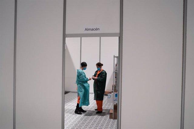 Dos trabajadores sanitarios hablan en las instalaciones del hospital de campaña instalado en IFEMA
