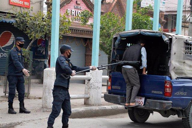Un policía de Katmandú detiene a un hombre por saltarse la cuarentena.