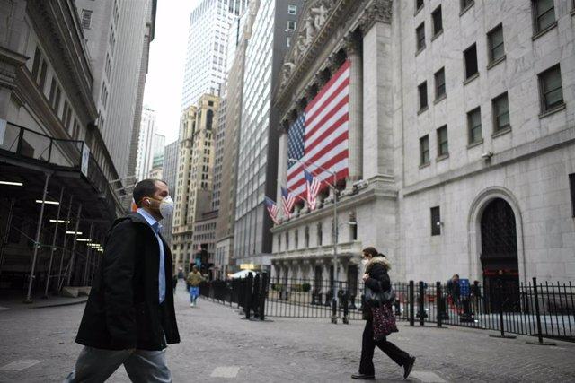 Un hombre con mascarilla atraviesa Wall Street